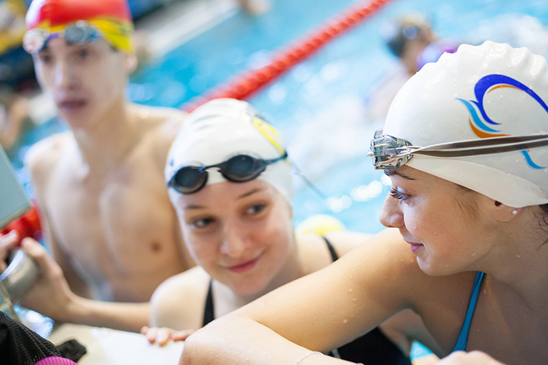 youth group swims in the pool wearing glasses and hat