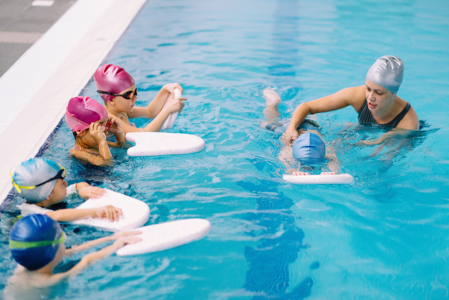 Group swimming lesson for children - swimming instructor working with one child, other kids watching. 5 to 6 years old children, indoor pool.
